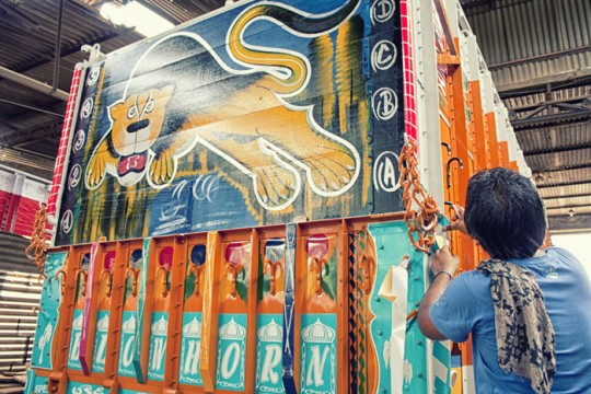 Putting vinyl on a truck back with lion painting